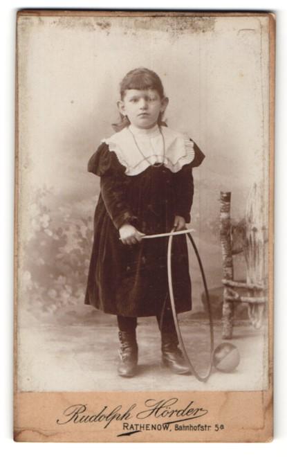 Fotografie Rudolph Hörder, Rathenow, kleines dunkelhaariges Mädchen mit Reifen
