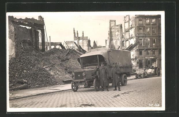Foto-AK Soldaten vor einem Bussing-Lastkraftwagen in einer zerstörten Stadt