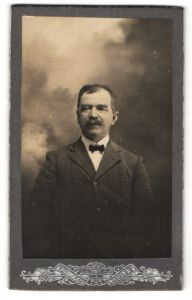 Fotografie F. de Leeuw, Salies-de-Bearn, Portrait Herr im Anzug mit Fliege vor Wolkenkulisse