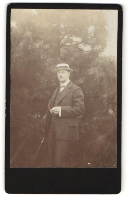 Fotografie Herr in Anzug mit Strohhut im Grünen
