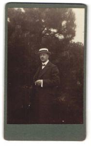 Fotografie Mann in Anzug mit Strohhut un Zigarette im Grünen
