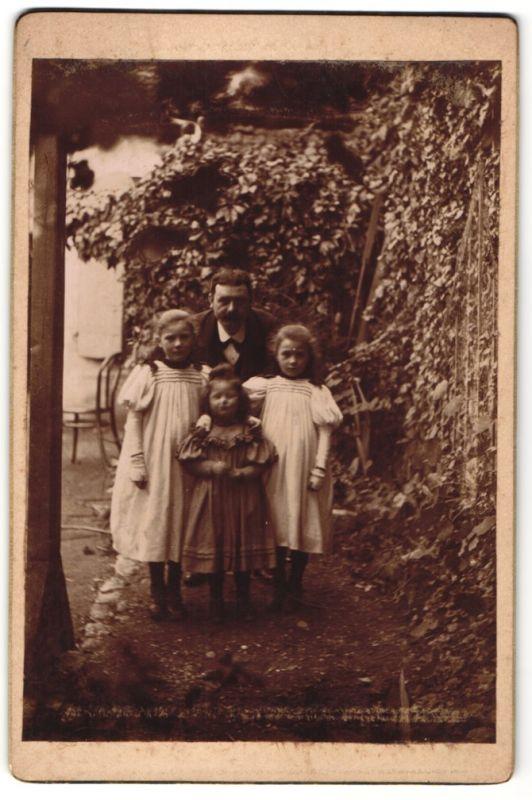 Fotografie Vater mit kleinen Töchtern im Garten
