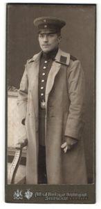 Fotografie Alfred Hirrlinger, Stuttgart, Portrait Soldat in Uniformmantel mit Schirmmütze