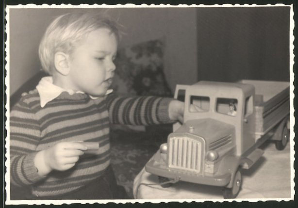 Fotografie Knabe spielt mit Spielzeug-Lastwagen
