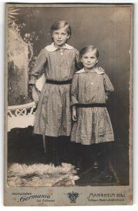 Fotografie Germania, Mannheim, Portrait zwei Schwestern in identischen Kleidern
