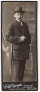 Fotografie Gebr. Strauss, Mannheim, Portrait halbwüchs. Knabe in Anzug mit Hut und Gehstock