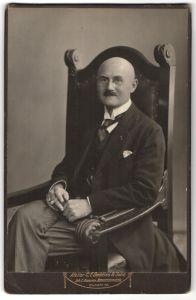 Fotografie C. F. Beddies & Sohn, Portrait bürgerlicher Herr auf Sitzmöbel