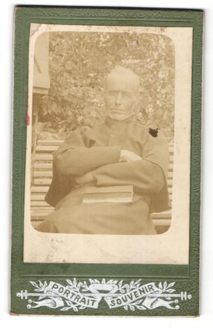Fotografie unbekannter Fotograf und Ort, Portrait betagter Geistlicher auf Parkbank sitzend