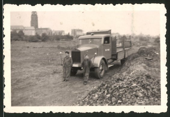 Fotografie Lastwagen MAN, LKW-Pritsche neben einer Schutthalde