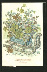Präge-AK Geschmückter Schlitten aus Vergissmeinnicht und Kleeblättern, Goldverzierung, Blumenbild