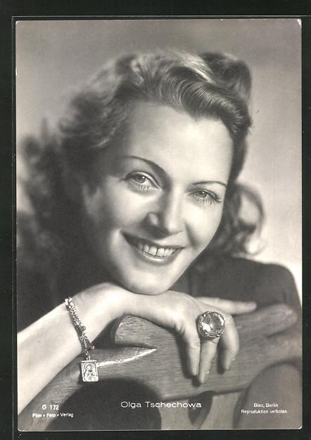 AK Schauspielerin Olga Tschechowa lächelnd den Kopf auf die Stuhllehne gelegt
