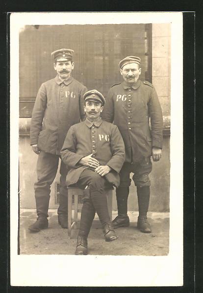 Foto-AK Drei Kriegsgefangene vor einer Mauer