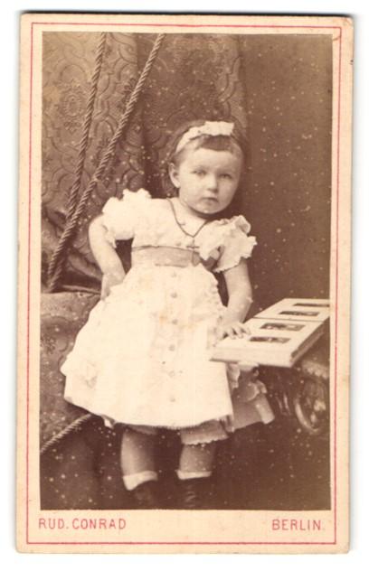 Fotografie Rud. Conrad, Berlin, Portrait kleines Mädchen mit Fotoalbum