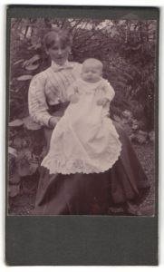 Fotografie unbekannter Fotograf und Ort, Portrait Frau mit Säugling im Garten