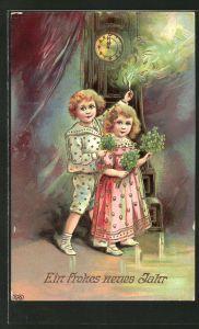 Präge-AK Neujahrsgruss, Kinder mit Glücksklee und Wunderkerze vor einer Standuhr