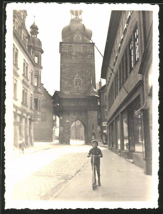 Fotografie Fotograf unbekannt, Ansicht Coburg, Kind mit Tretroller vor dem Torturm