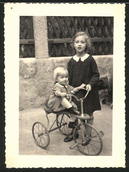 Fotografie Mädchen & Baby spielen mit einem Dreirad