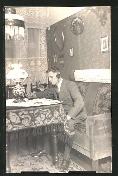 AK junger Mann liest Zeitung und hört dabei Radio