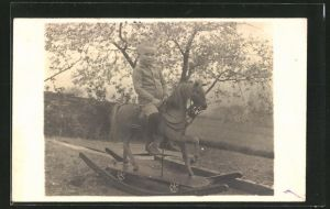 Foto-AK Bub auf Schaukelpferd im Garten