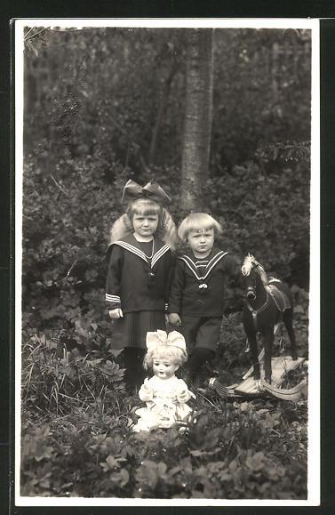 Foto-AK Geschwister in Matrosenanzügen mit Schaukelpferd und Puppe