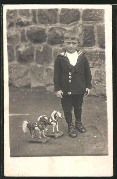 Foto-AK Junge im Matrosenanzug mit Spielzeugpferden