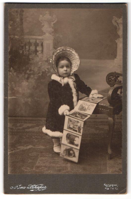 Fotografie Max Schaper, Schwerin, Portrait kleines Mädchen in Wintermantel mit Haube und Fotoalbum