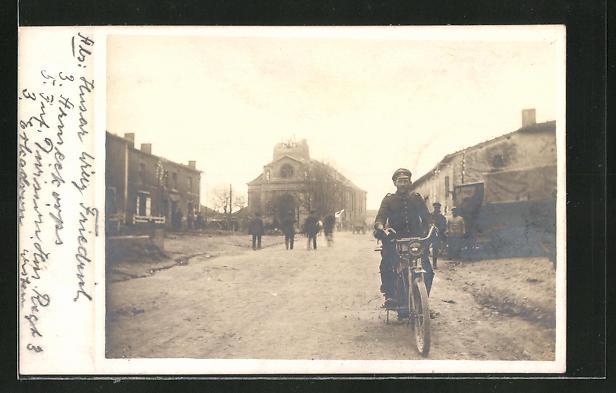 AK Soldat fährt auf einem Fahrrad durch eine Strasse mit zerstörten Häusern