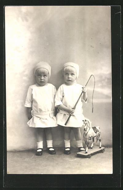 AK zwei Mädchen mit Schaukelpferd und Peitsche