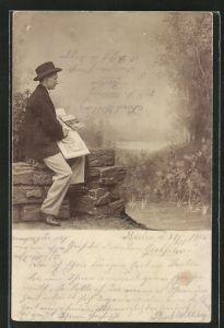 Foto-AK Mann mit Hut auf Mauer sitzend und malt, Studiokulisse