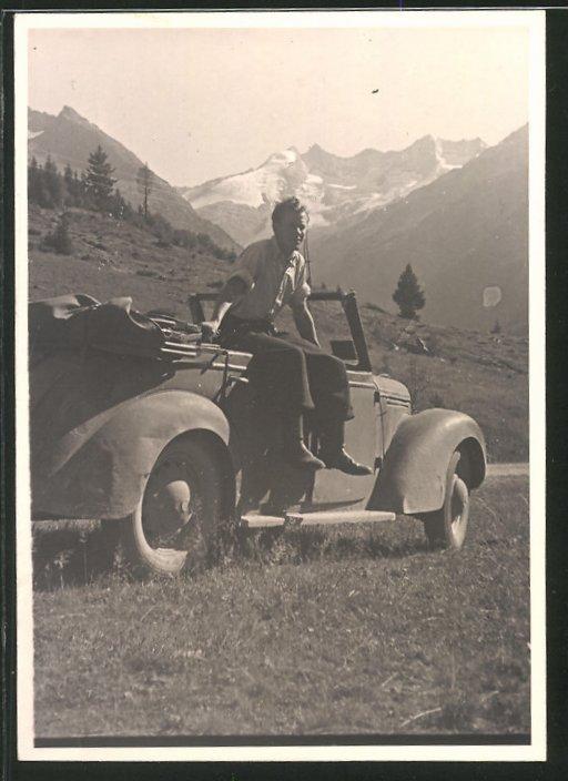 Fotografie Auto Cabrio, Fahrer sitzt lässig am PKW vor Gebirgspanorama