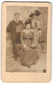 Fotografie unbekannter Fotograf und Ort, Portrait junger Herr und zwei Damen mit Hüten und Handtaschen