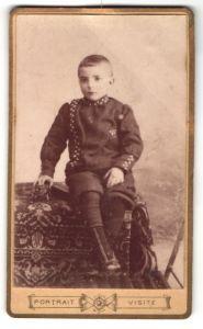 Fotografie Portrait Visite, Ort unbekannt, niedlicher Knabe mit kurzem Haar im interessanten Anzug und Spielzeugauto