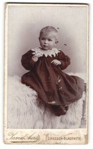 Fotografie James Aurig, Dresden-Blasewitz, niedliches blondes Kleinkind im schwarzen Kleid mit weissem Spitzenkragen
