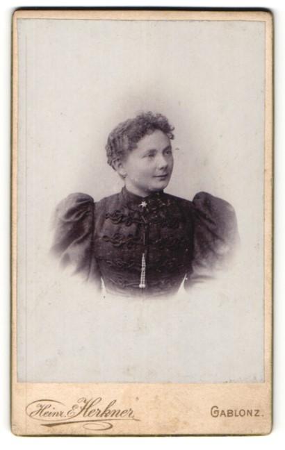 Fotografie Heinr. Herkner, Gablonz, Portrait Frau mit zusammengebundenem Haar