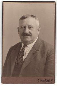 Fotografie Georg Koczyk, Coswig, Portrait stattlicher Herr mit Oberlippenbart und Krawatte im Anzug