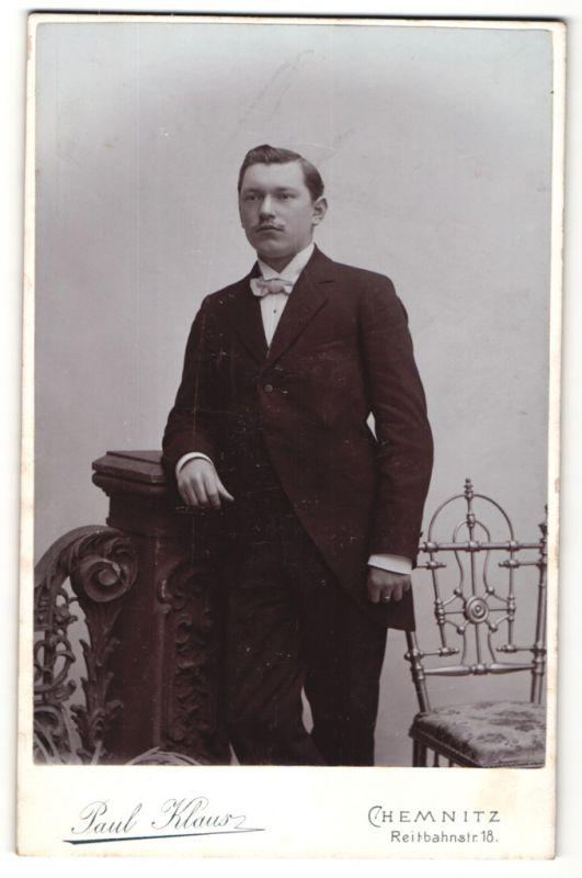 Fotografie Paul Klaus, Chemnitz, junger dunkelhaariger Mann mit Schnauzer und Fliege im schwarzen Anzug