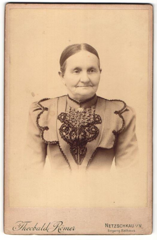 Fotografie Theobald Römer, Netzschkau i. V., Portrait betagte Dame mit zurückgebundenem Haar und Stickerei an der Bluse