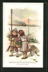 AK Neujahrsgruss, Junge und Mädchen mit Schlitten und Korb Glücksklee