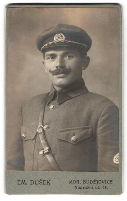 Fotografie Em. Dusek, Mor. Budejovice, Portrait Soldat in Uniform mit Schirmmütze