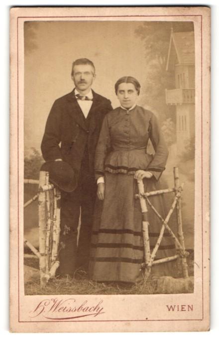 Fotografie H. Weissbach, Wien, hübsches Paar in edler Kleidung am Holzzaun stehend