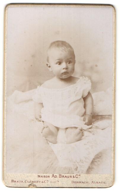 Fotografie Braun, Dornach Alsace, Kleines Baby in weissem Kleidchen schaut verdutzt in Richtung Kamera