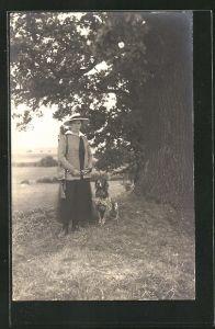 Foto-AK Jägerin mit Gewehr und Hund unter einem Baum