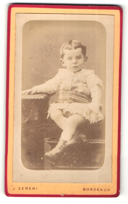 Fotografie J. Sereni, Bordeaux, Junger Knabe mit Kleidchen sitzend