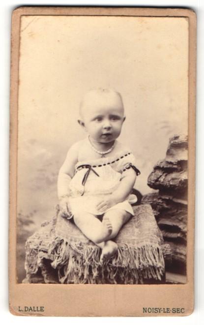Fotografie L. Dalle, Noisy-le-Sec, Kleinkind mit Perlenkette auf Mauer sitzend