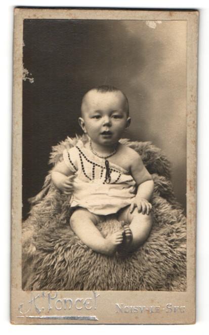 Fotografie A. Poncet, Noisy-le-Sec, Baby auf einem grossen Fell sitzend