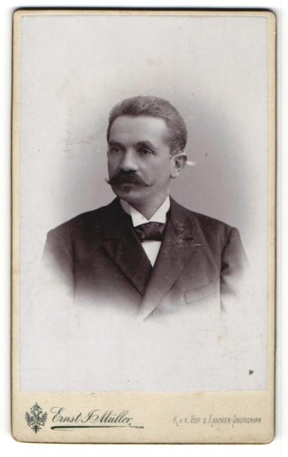 Fotografie Ernst J. Müller, Reichenberg, Portrait charmanter Herr mit Schnurrbart im schwarzen Anzug