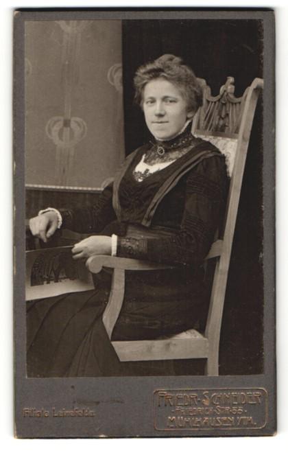 Fotografie Friedr. Schneider, Mühlhausen i. Th., charmant lächelnde Dame mit Zeitschrift im Stuhl sitzend