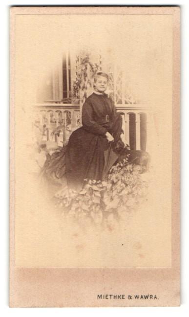 Fotografie Miethke & Wawra, Wien, lächelnde Dame mit Schirm am Geländer stehend