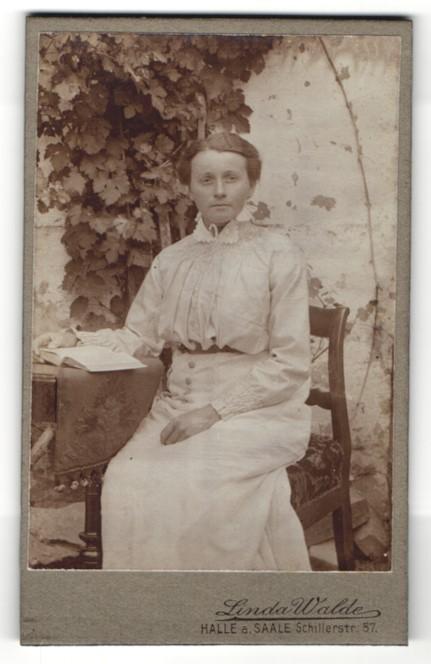 Fotografie Linda Walde, Halle / Saale, hübsche Dame mit Buch vor dem Haus sitzend