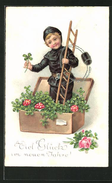 AK kleiner Schornsteinfeger steht in einer Kiste mit Kleeblättern und Fliegenpilzen